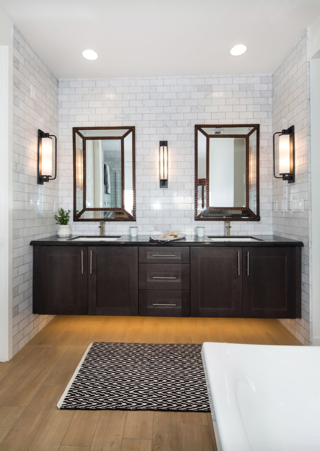 hardwood veneer flooring in modern farmhouse bathroom with white subway tile