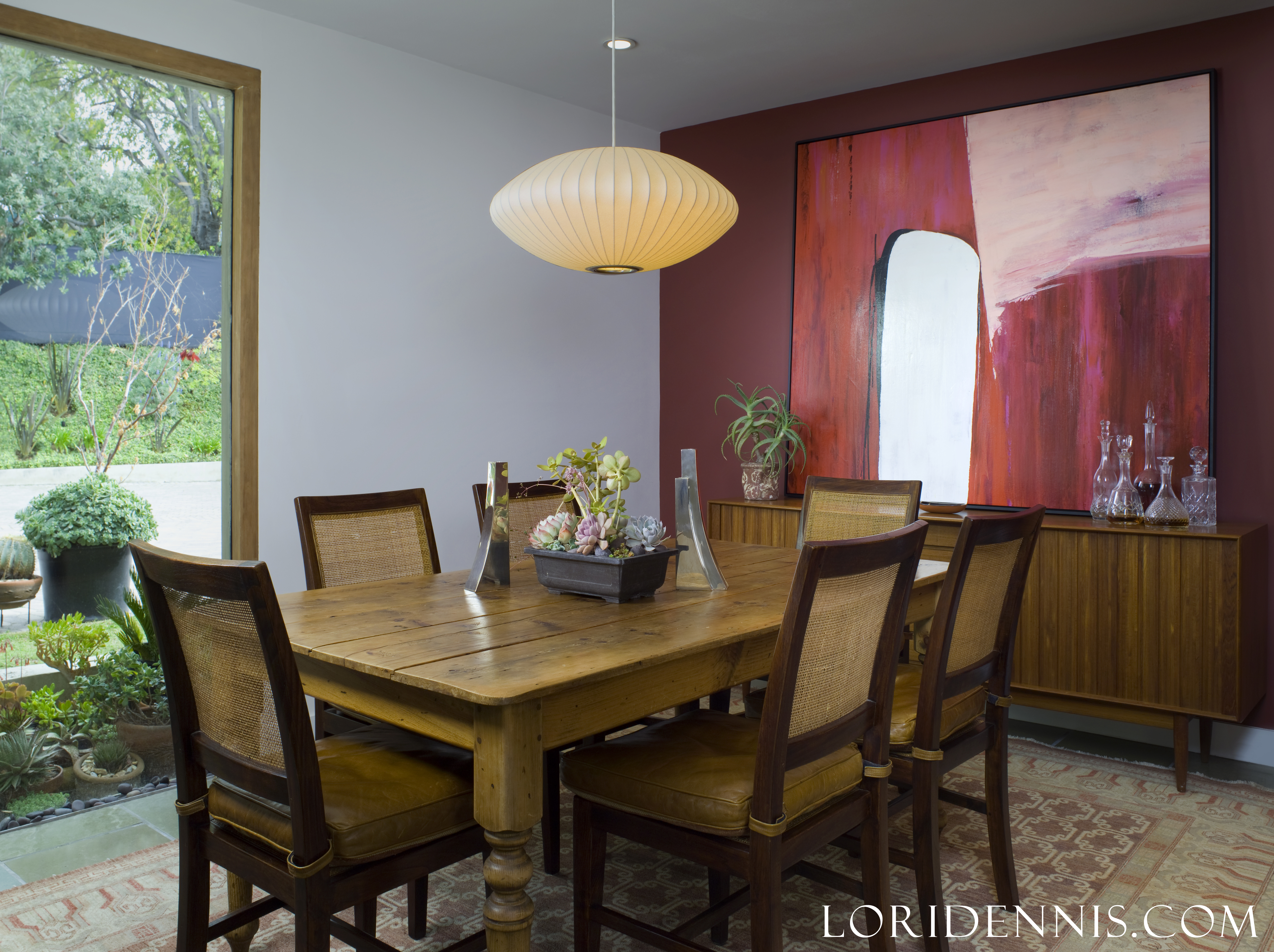 zen asian dining room with red wall and art