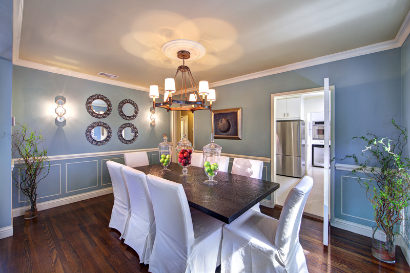 Dining room with Blue Walls and white slip covered chairs in Hollywood